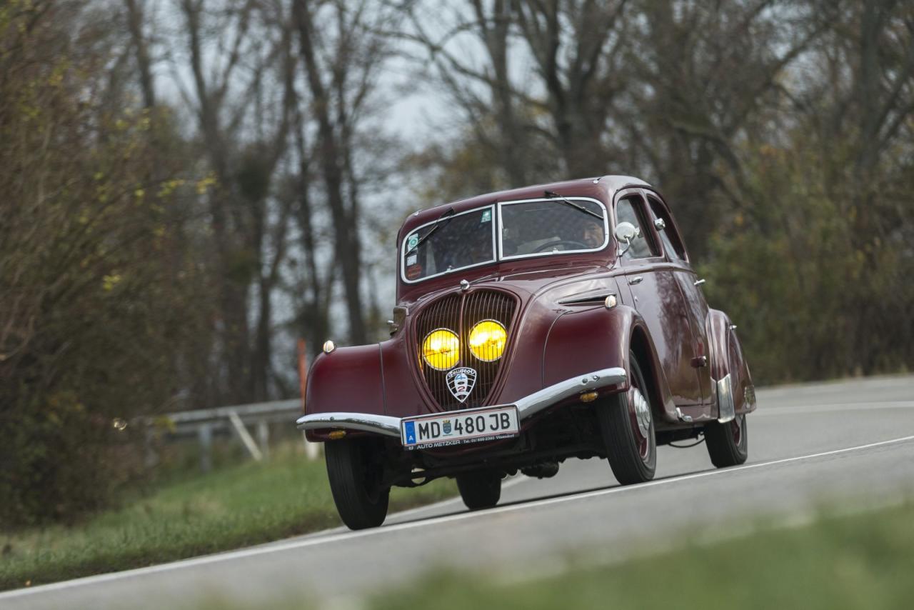 Vorkriegsautos schauen anders aus, niemand glaubt dem Peugeot 402 sein Alter. Luftwiderstand 0,68 ergibt Jahrzehnte später die Nachuntersuchung in einem windigen Kanal. Gelbes Licht ist seit 1936 der Franzosen Brauch, Brüsseler Harmonisierungs-Neurotiker stellen  das erst 1993 ab. Scheinwerferaugen hinterm Kühlergrill, gut geschützt gegen Steinschlag  und Wildtiere. Darunter das Pannenhilfeloch  zur Starterkurbel.