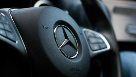 Mercedes-Emblem auf dem Lenkrad eines Autos.